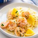 lemon garlic shrimp pasta on a white plate with lemon slices