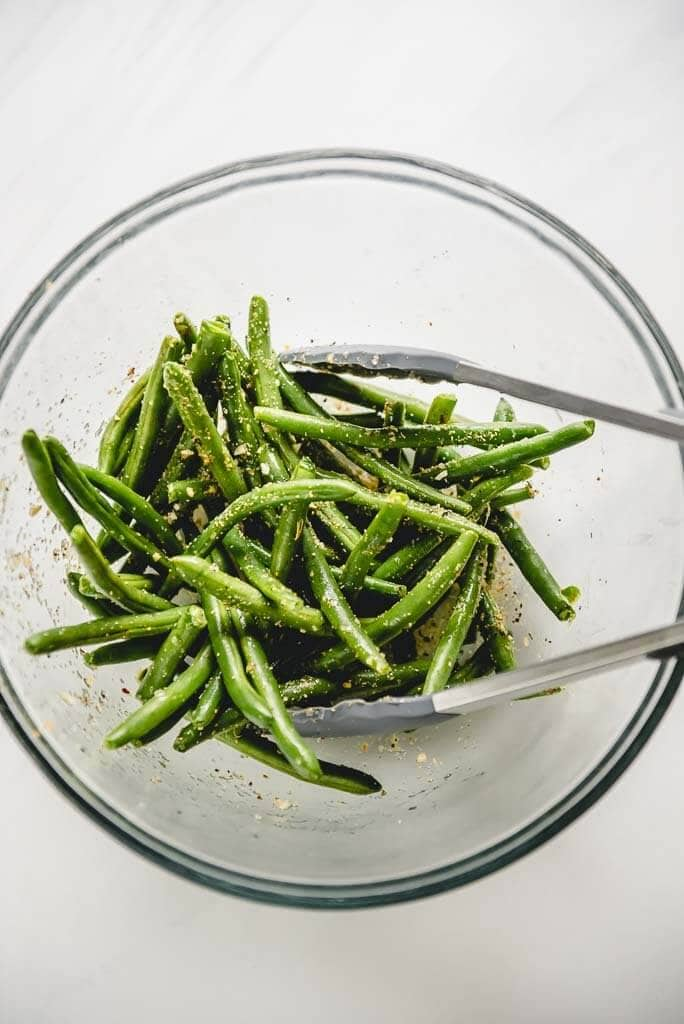 green beans tossed with seasoning in a glass bowl with tongs