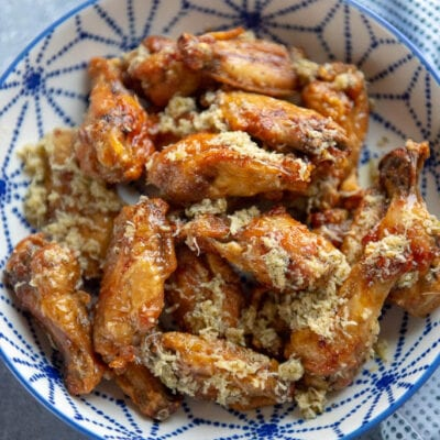 chicken wings with garlic and parmesan in a blue and white bowl