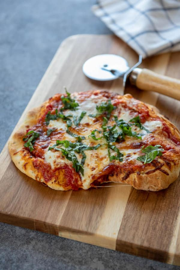 air fryer margherita pizza on cutting board with pizza cutter