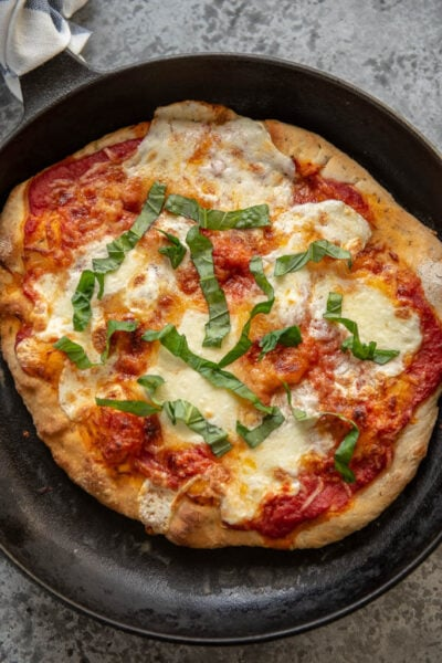 cast iron skillet with Margherita pizza topped with fresh basil