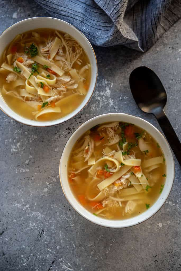two bowls of chicken noodle soup on gray table with black spoon