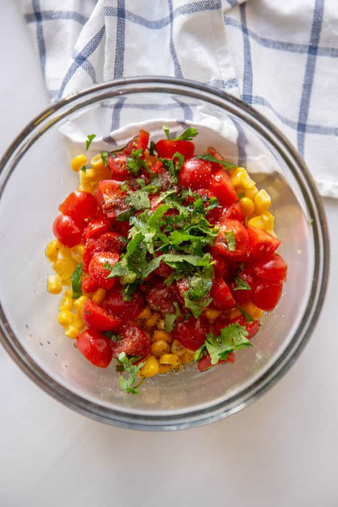 fresh corn, tomatoes and cilantro in glass bowl for salsa