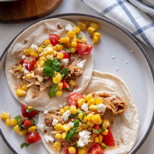 chicken tacos with corn salsa on white plate