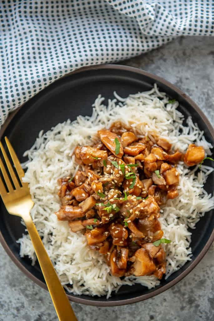 honey garlic chicken over rice on black plate