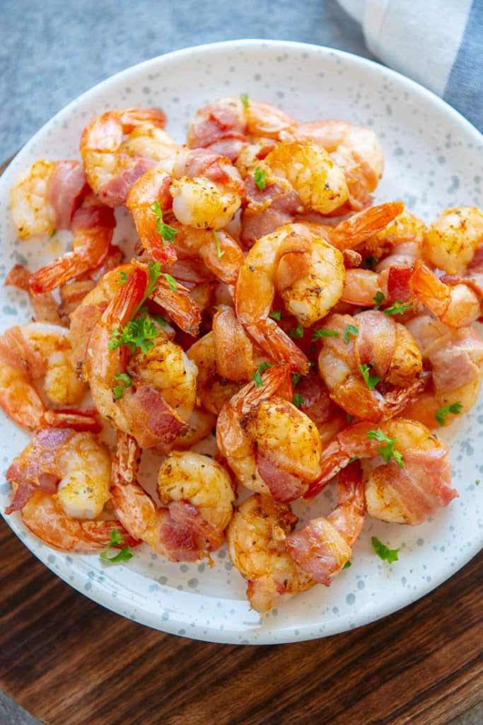 White and blue platter filled with air fryer bacon wrapped shrimp