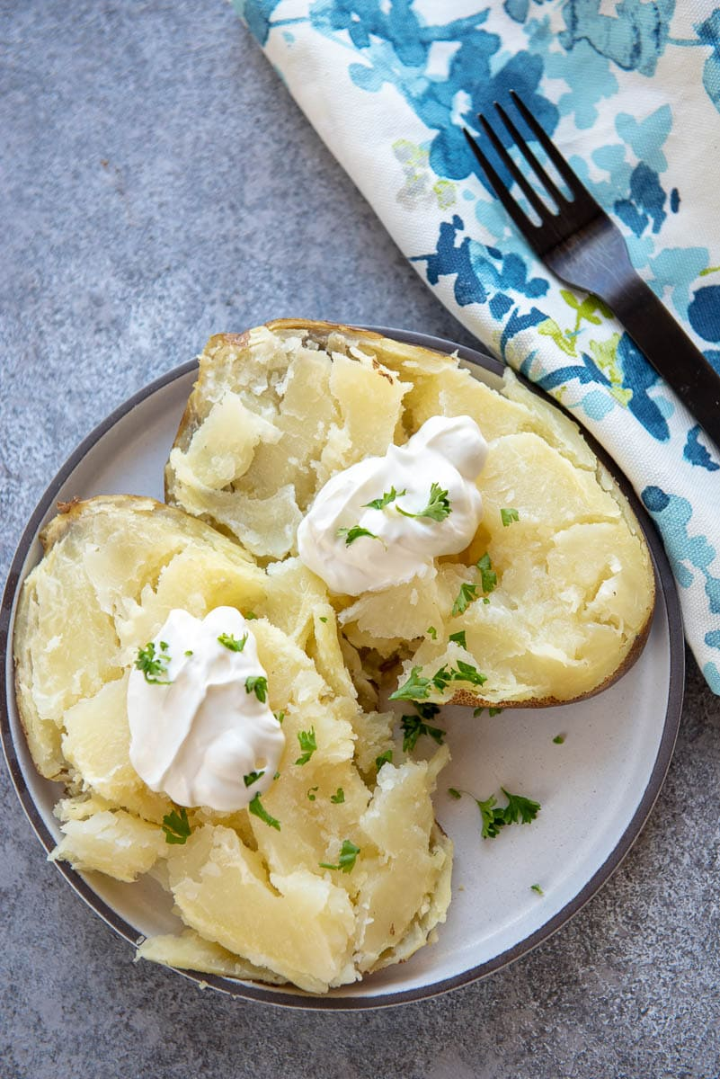 plate with baked potato cut in half with sour cream