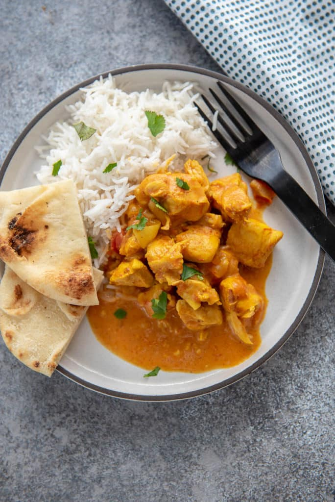butter chicken with rice and naan on white plate