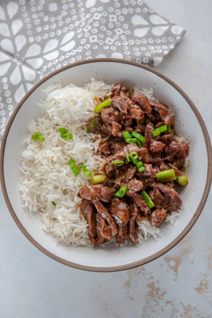 Mongolian beef with rice and green onions in white bowl
