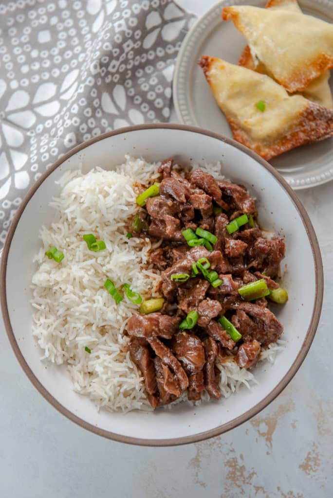 serving of Mongolian beef with rice and side of two crab rangoons