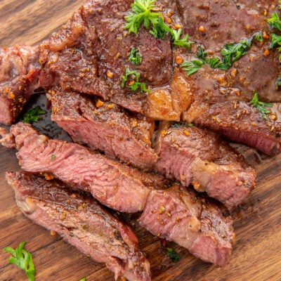 sliced ribeye steak on wood cutting board
