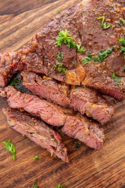sliced ribeye steak on wood cutting board