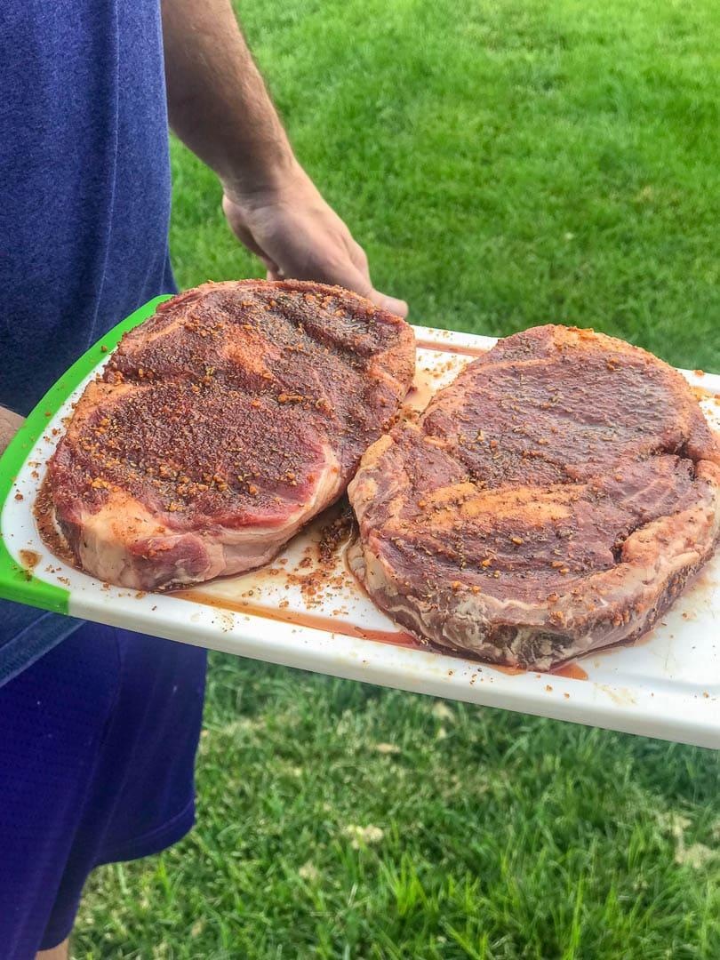 2 ribeye steaks on board ready for grill