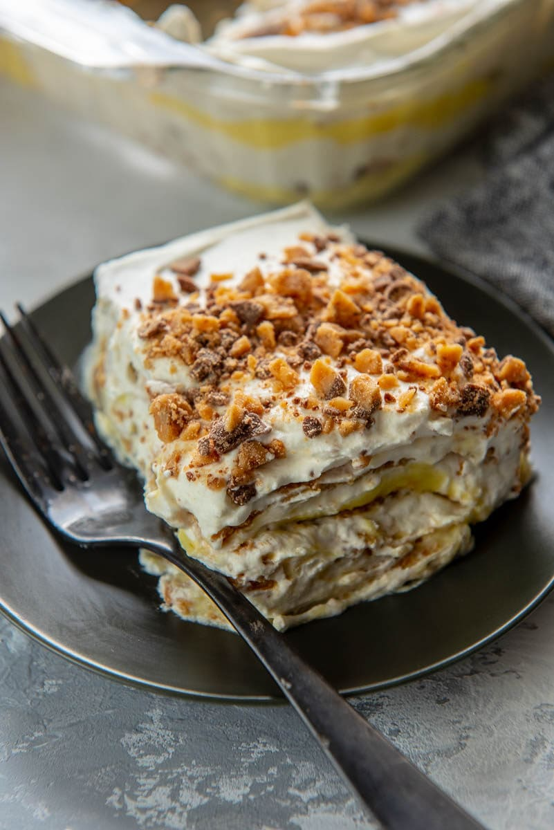 square slice of icebox cake with toffee bits on top on black plate