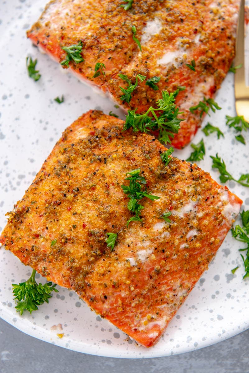 piece of grilled salmon on plate with parsley