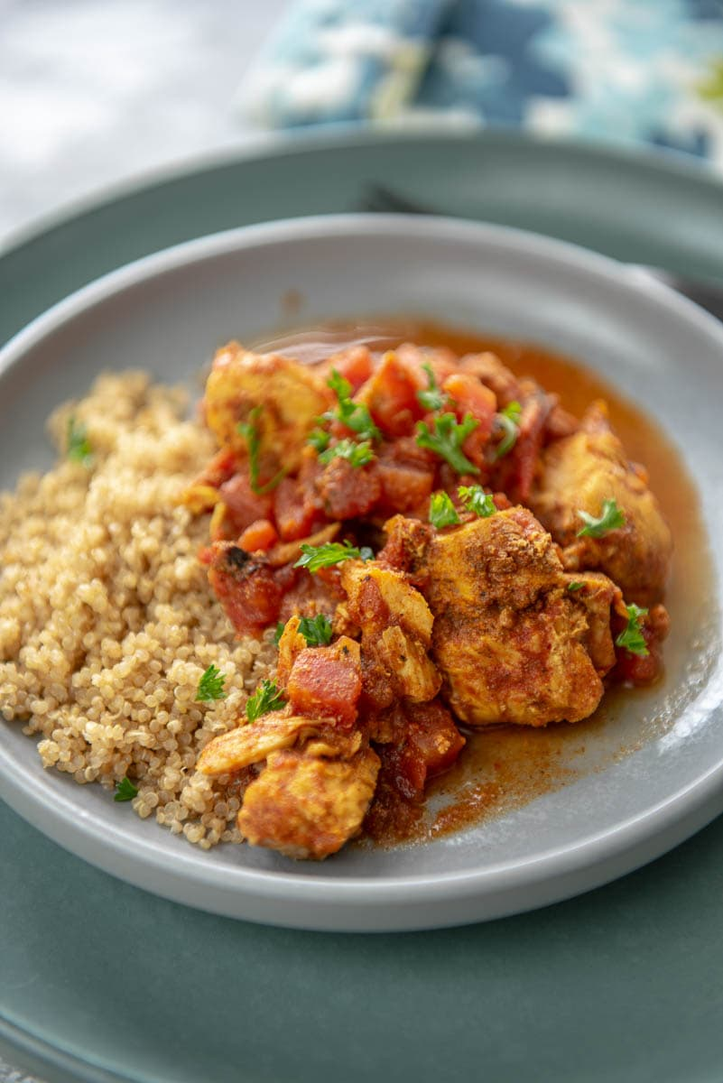 plate with quinoa topped with moroccan chicken and parsley