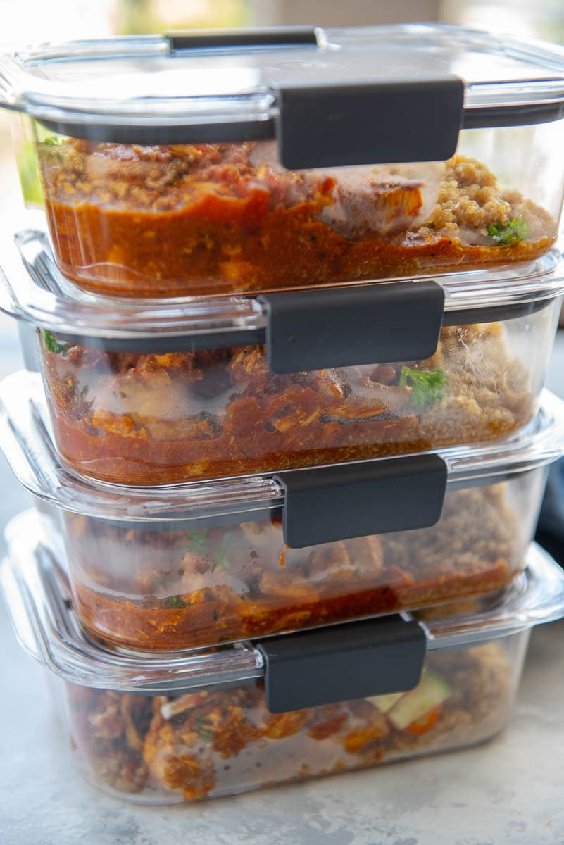 clear food containers stacked and filled with Moroccan chicken and quinoa