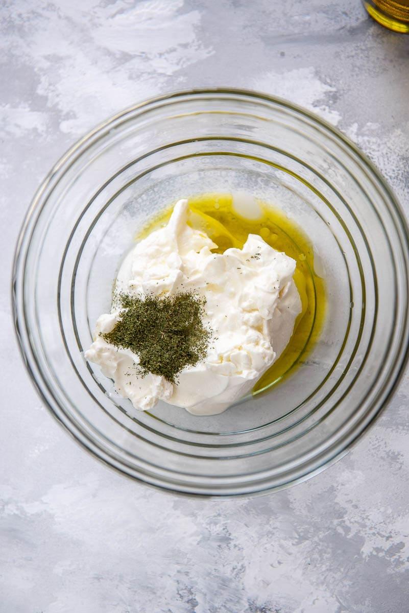 yogurt, olive oil and seasoning in glass bowl