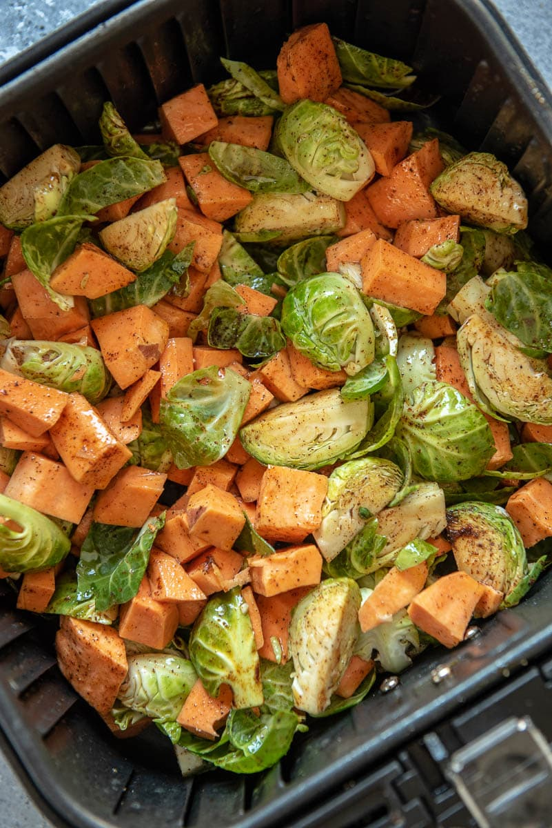 raw sweet potatoes and Brussels sprouts in air fryer basket ready to cook