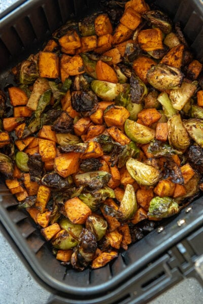 sweet potatoes and Brussels sprouts in air fryer basket
