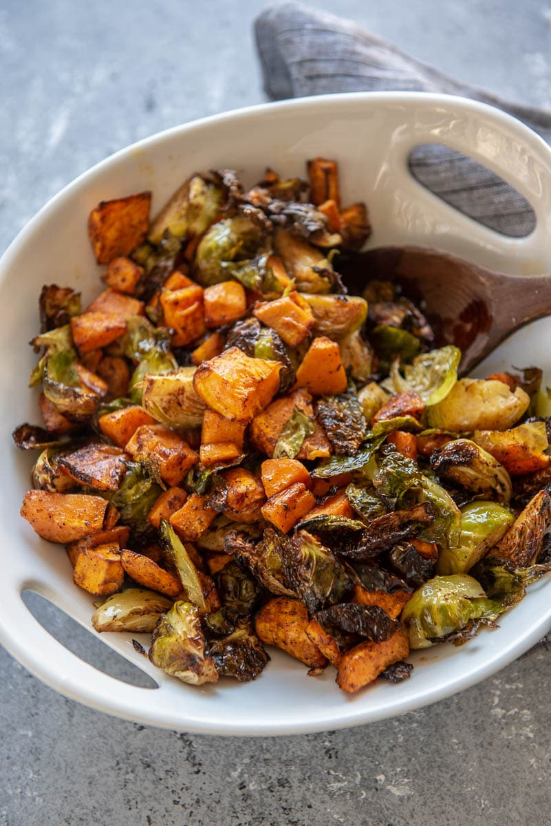 roasted brussels sprouts and sweet potatoes in a white serving bowl