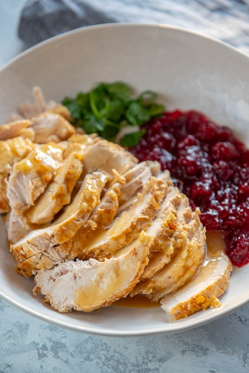 sliced turkey breast with gravy and cranberry sauce in white bowl