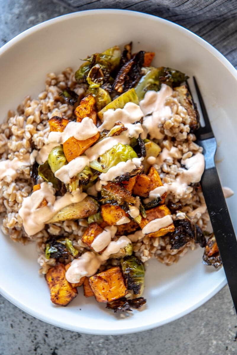 white bowl with farrow, sweet potatoes, Brussels sprouts and sriracha mayo