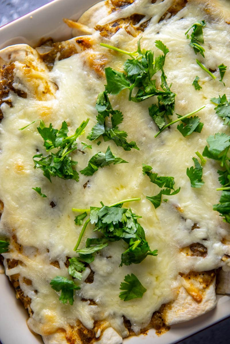 casserole dish with turkey enchiladas topped with cilantro