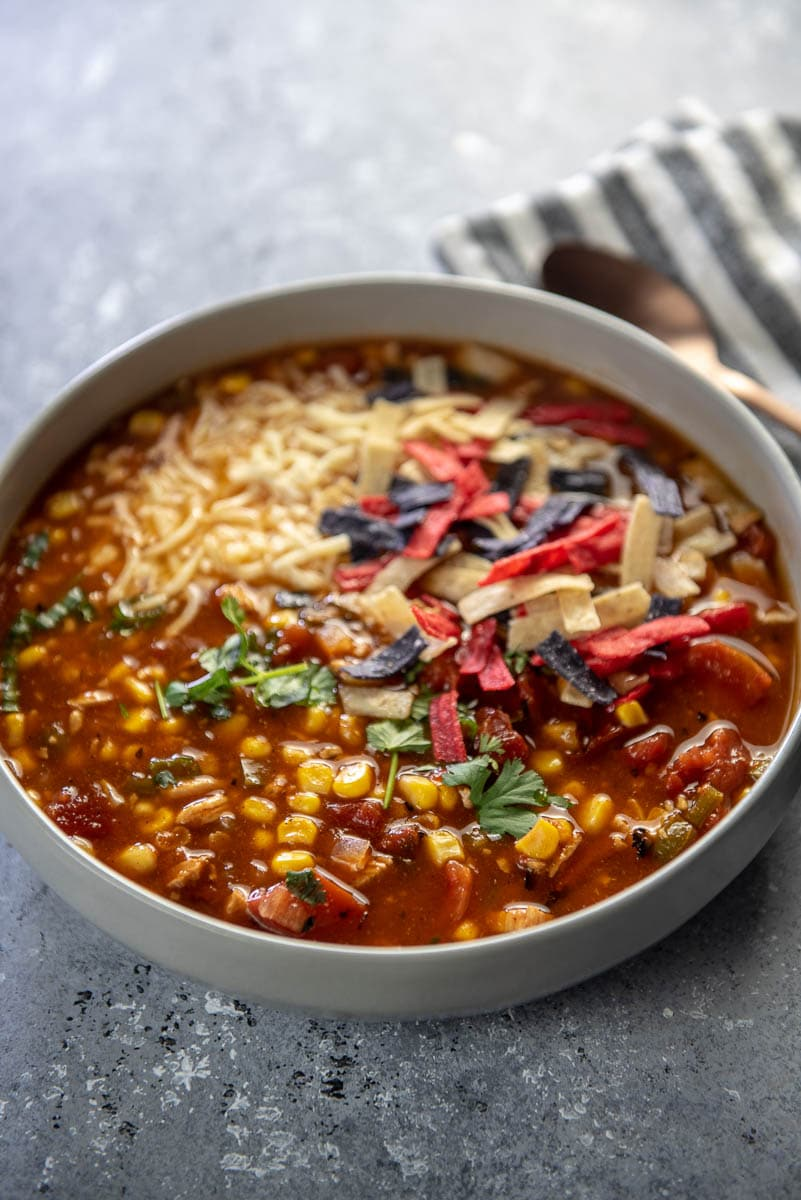 bowl of turkey tortilla soup with cheese and tortilla strips