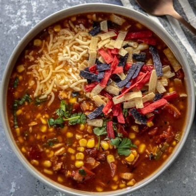turkey tortilla soup in gray bowl topped with cheese and tri-color tortilla strips