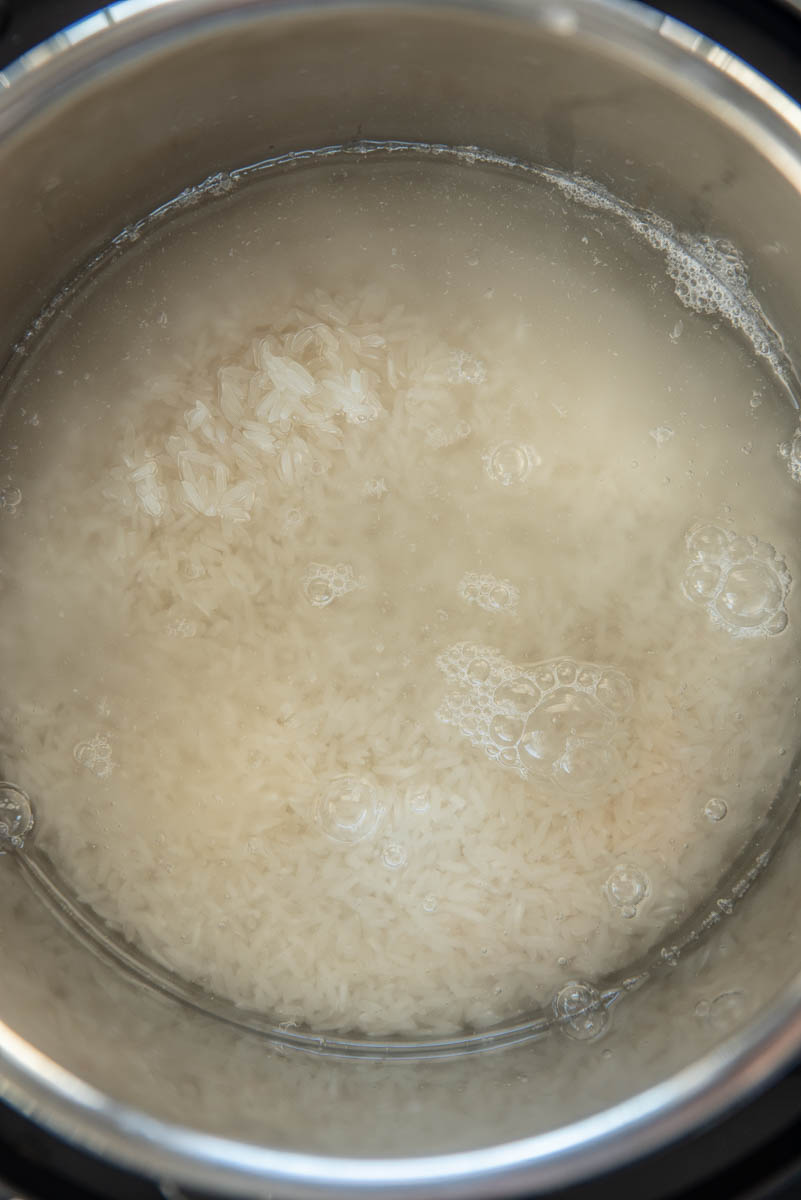 uncooked rice and water in pressure cooker pot