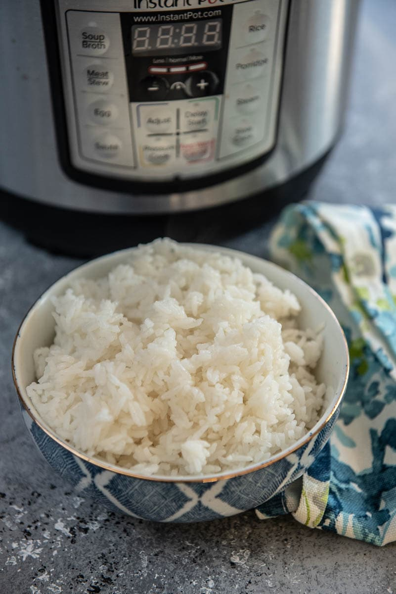 blue bowl of cooked rice next to instant pot
