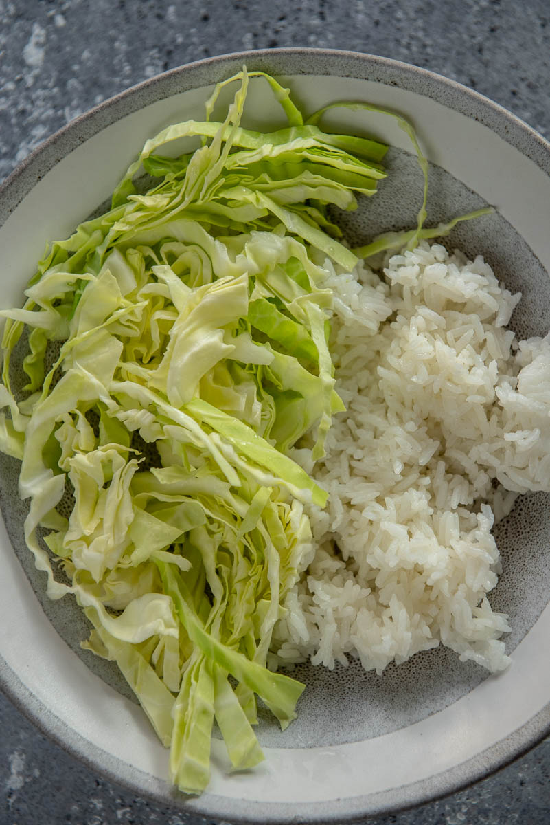 white rice and cabbage in gray and white bowl