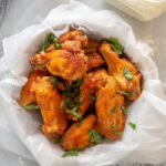 buffalo chicken wings in round bowl wrapped in paper