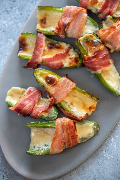 jalapeño popper wrapped in bacon on gray platter
