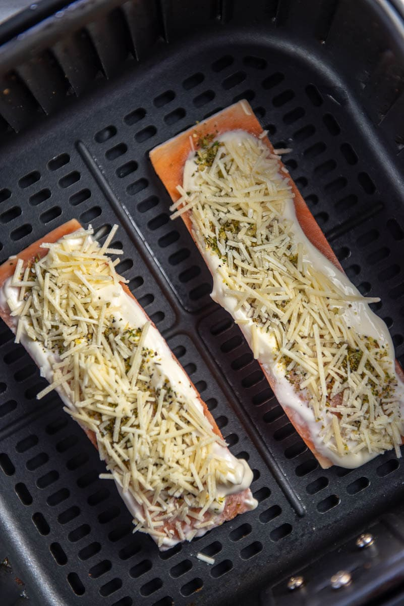 salmon topped with mayo cheese and seasoning in air fryer basket ready to cook