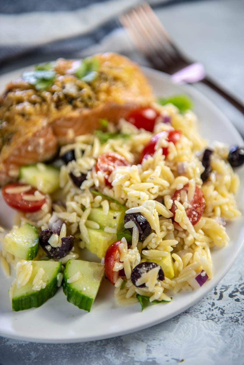 Orzo salad with cucumbers and tomatoes on white plate with salmon