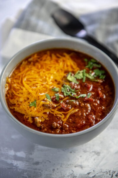 beef chili topped with cheese in gray bowl