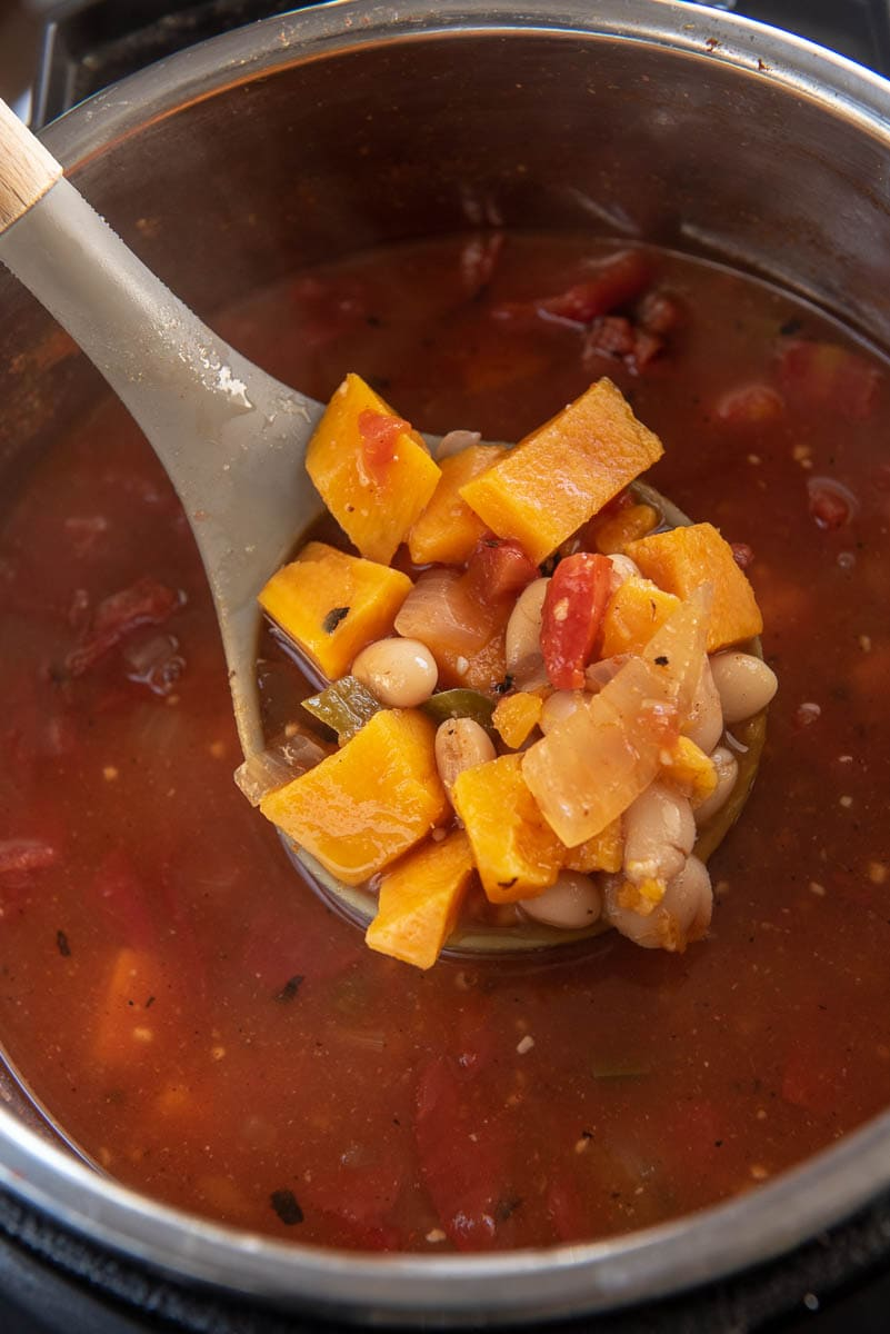 ladle in instant pot of vegetarian tortilla soup with sweet potatoes