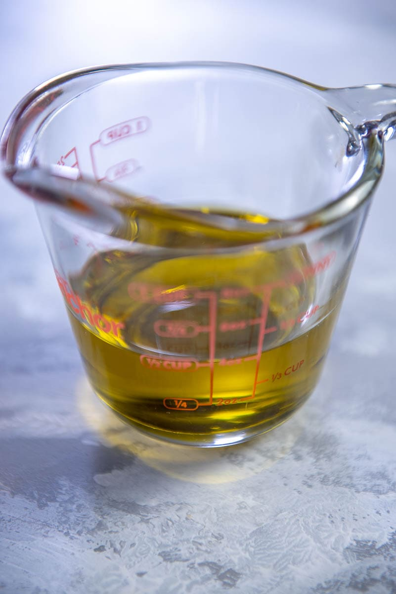 measuring cup with 1/2 cup olive oil