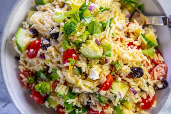 orzo salad with tomatoes cucumbers and feta in gray and white serving bowl