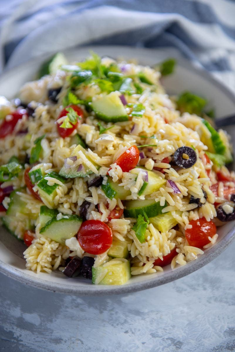 orzo salad with tomatoes and cucumbers in gray bowl