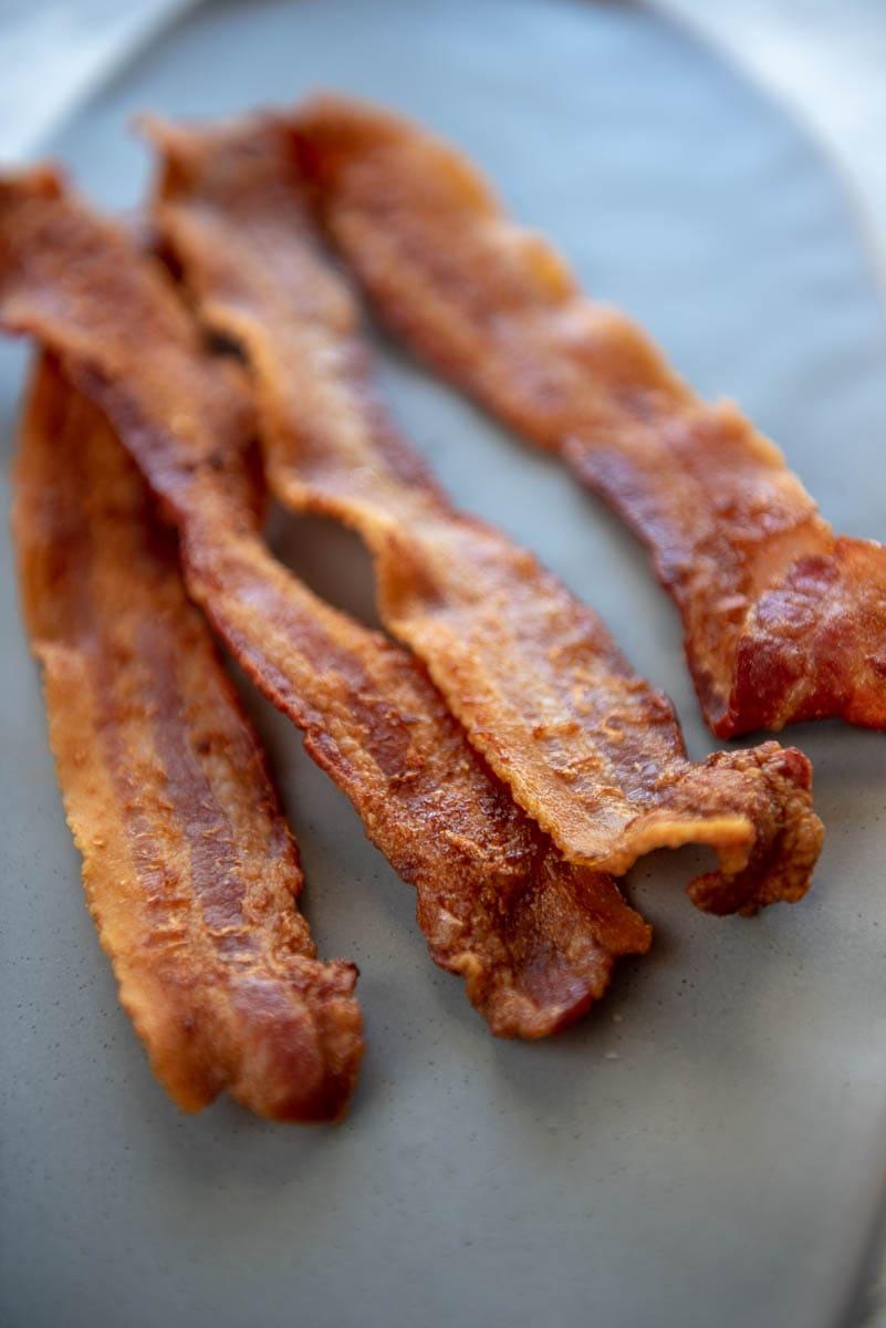 4 strips of crispy bacon on a gray platter