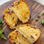 sourdough grilled cheese sandwich halves arranged on wood platter with parsley garnish