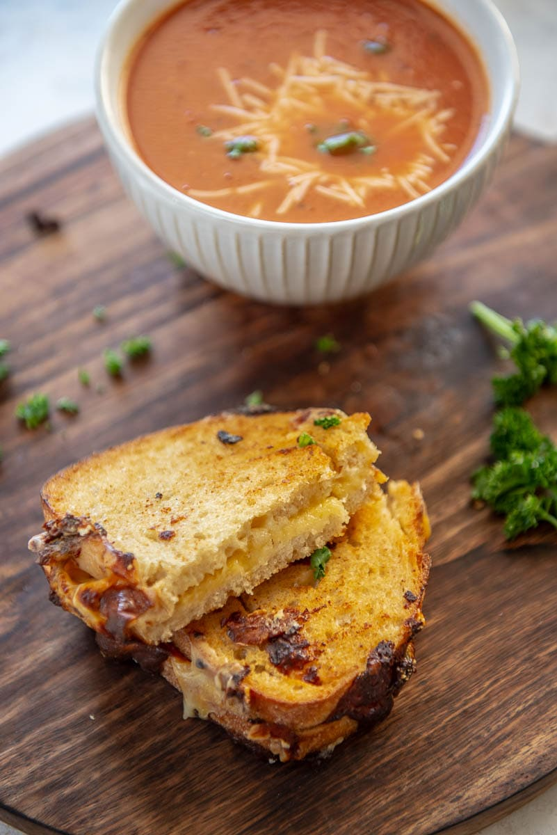 grilled cheese on wood platter with bowl of tomato soup