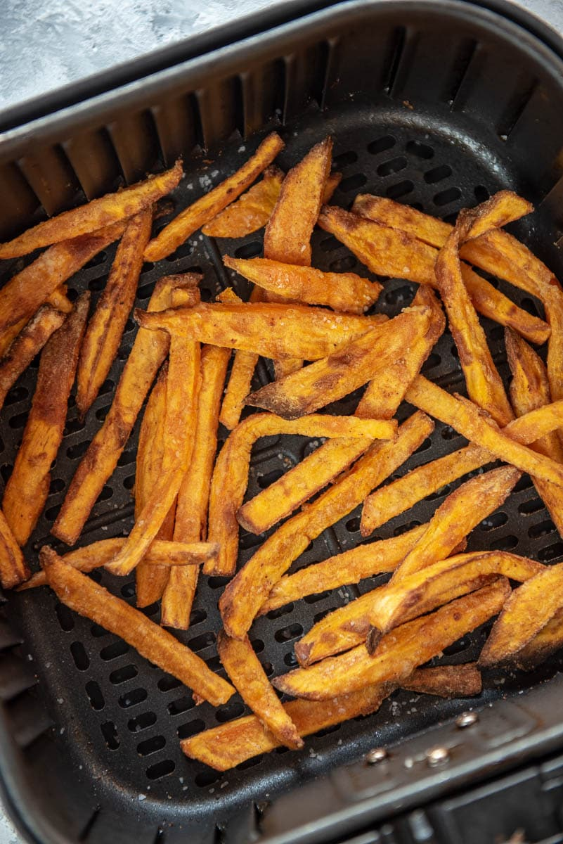 air fryer basket filled with sweet potato fries