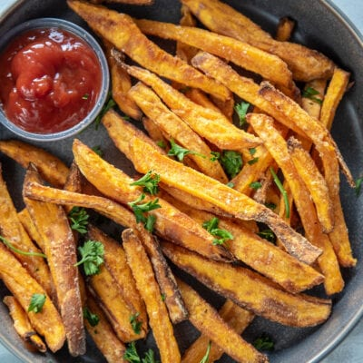 gray bowl with sweet potato fries and a container of ketchup