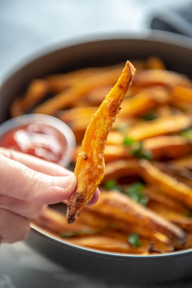 holding a single sweet potato fry