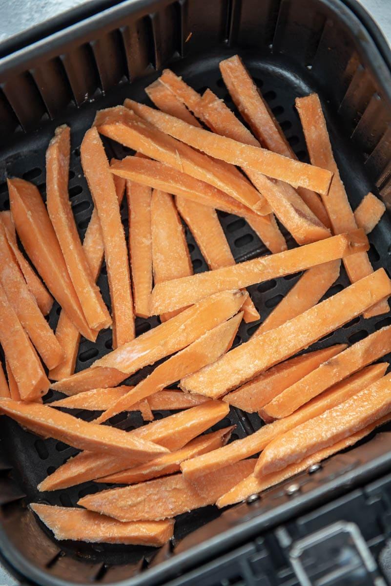 raw sweet potato fries in air fryer basket
