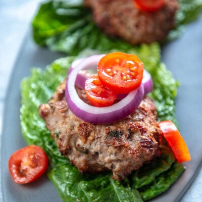 gray platter with lettuce wrapped turkey burger patties with tomato and onion